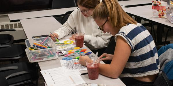 Two girls coloring at a Wellness Wednesday event