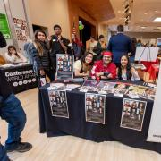 Students on the Cultural Events Board sit at their table at the spring Involvement Fair
