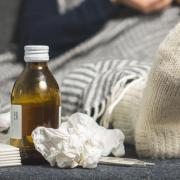 Sick person on couch with cold care supplies
