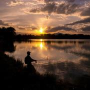 Person fishing in a lake at sunset.