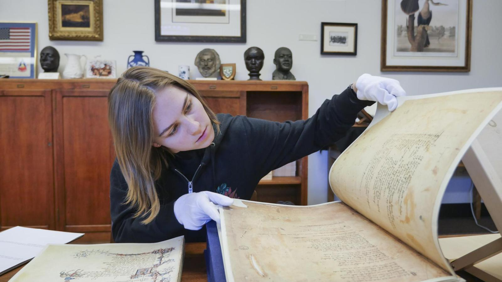 Student looks through old history book with gloves