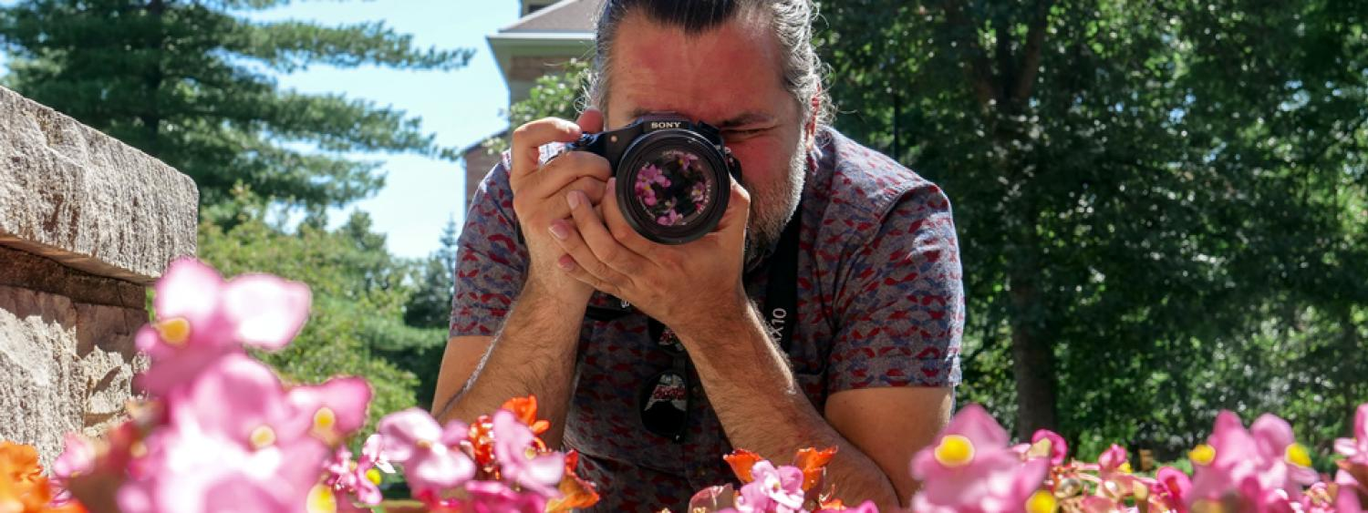 Student using a camera to take a picture of pink flowers.