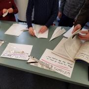 A desk with paper and students working on paper airplanes.