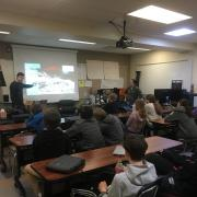 Students are watching a presentation about space. One of the presenters is generally gesturing towards the screen.