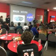 Students sit at round red tables watching 3 presenters: 2 guys, 1 girl. The screen has the NASA logo.