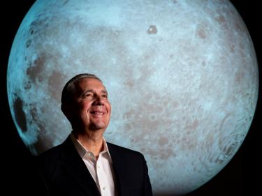 Dr. Jack Burns photo with Moon on Science on the Sphere in the background