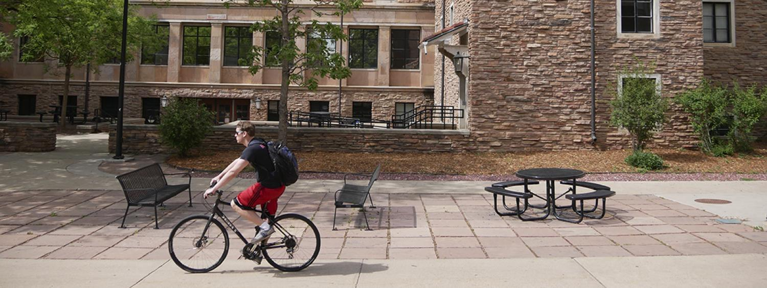 student biking on sidewalk next to dormitory