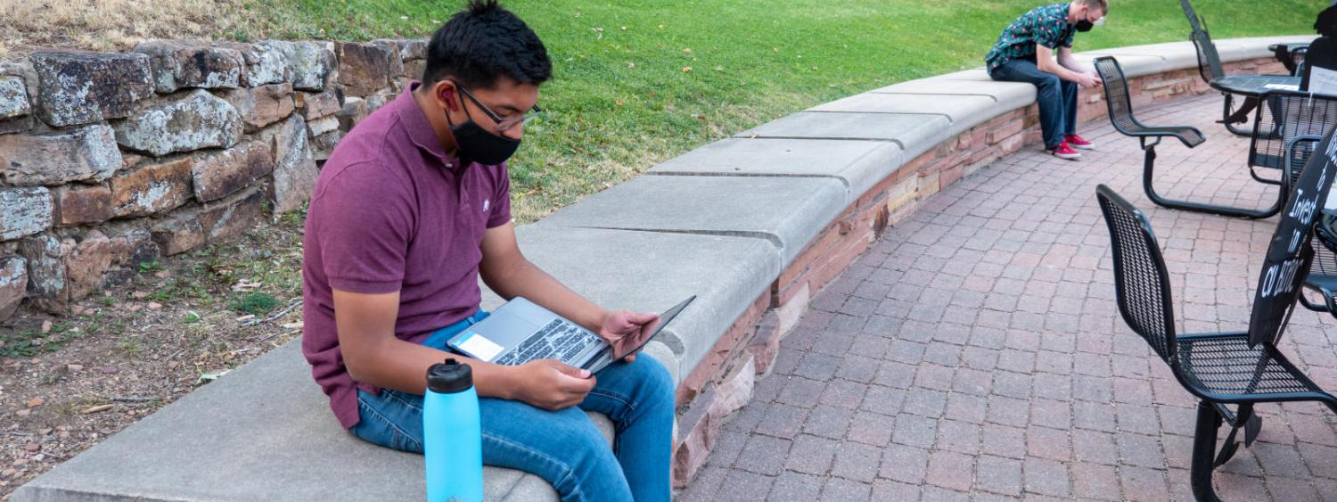 student with mask sits on lawn with computer