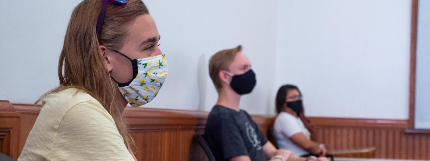 students 6 ft apart wearing masks in class looking at teacher