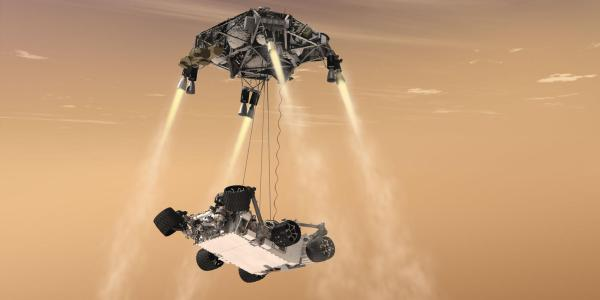 Artist illustration of Mars Rover landing on Mars from a tether attached to a craft with retrorockets.
