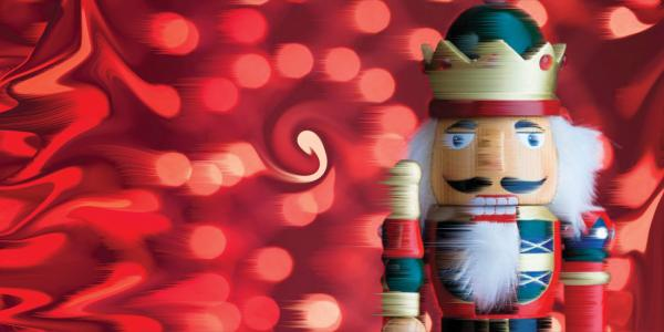 Nutcracker figure in front of red light background