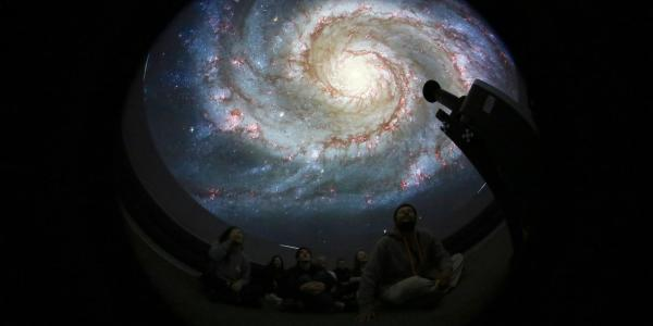 Inside Fiske Minidome image of M51 galaxy on dome and students looking up