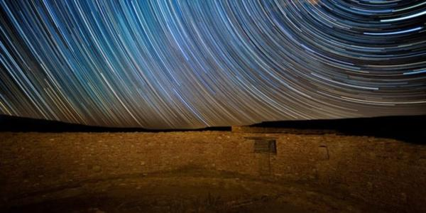 Photo of the night sky and star trails from the southwestern United States rock formation in the foreground