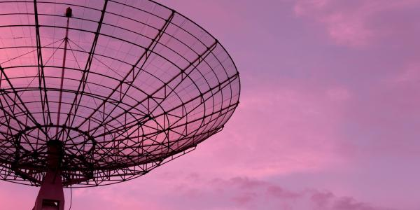 Photo of a radio dish against a pink sunset sky