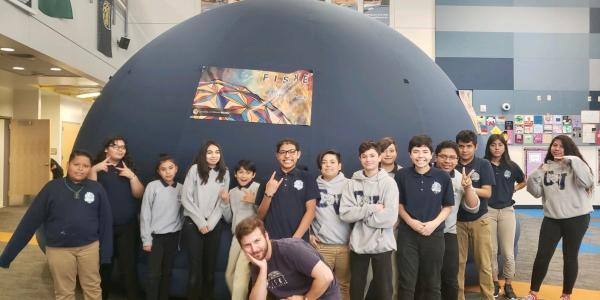 Photo of Fiske Minidome at School with our presenter Max and students by dome