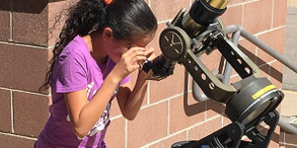 Photo of young girl looking through a solar telescope