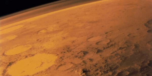 Artist illustration of a portion of Mars from orbit. Craters in view, mountains and the thin atmosphere.