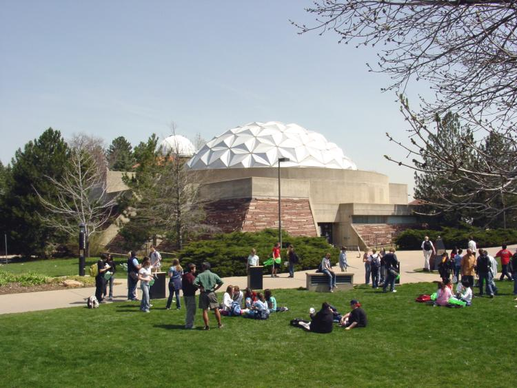 Fiske Planetarium with group of students sitting in grass outside.