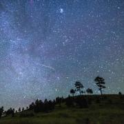 Photo of the night sky with grassy hill and trees and a meteor in the sky