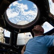 Photo on board the ISS astronaut looking out the cupola windows at earth