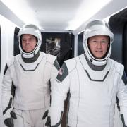 NASA astronauts Bob Behnken, left, and Doug Hurley, wearing SpaceX spacesuits, walk through the Crew Access Arm connecting the launch tower to the SpaceX Crew Dragon spacecraft during a dress rehearsal at NASA's Kennedy Space Center in Florida on Jan. 17, 2020. Credits: SpaceX