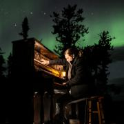 Roman Zavada playing the piano with the aurora borealis on the theater screen in the background.