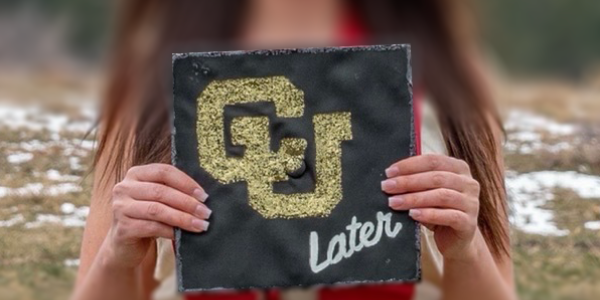 student holding mortarboard with CU Later printed on it