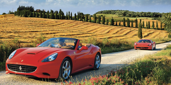 Two expensive red covertables driving down an Italian country road