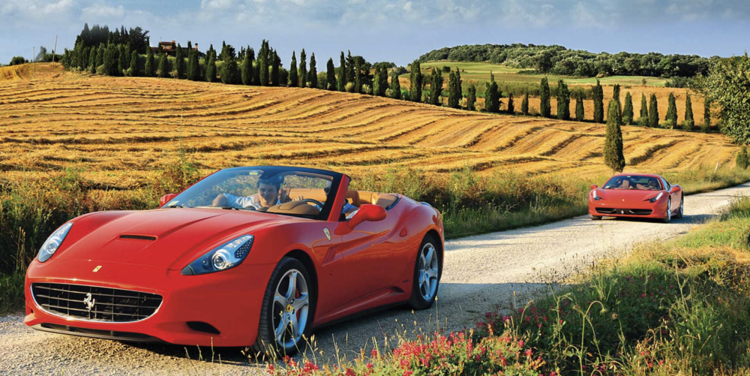Expensive new red convertable cars driving down an a road in the country side in Italy.