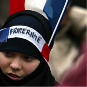 Musilum woman standing in a crowd in front of a French flag