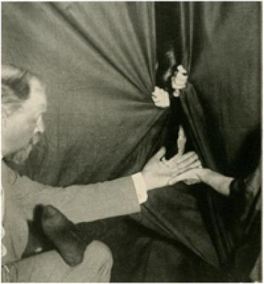 A flashlight photograph of Eva producing ectoplasm from the medium's cabinet. Schrenck-Notzing appears on the left. Image courtesy of Hathi Trust.