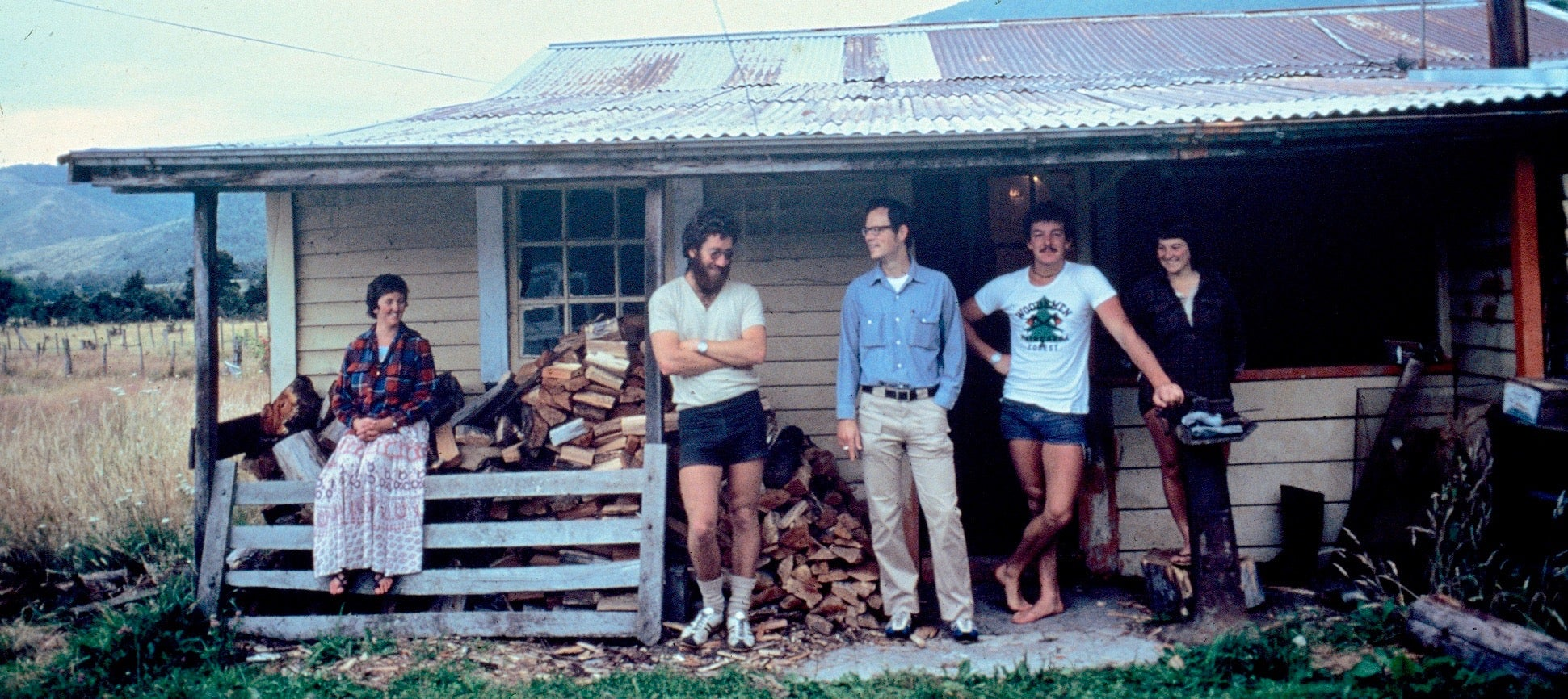Group standing on front porch of old house in New Zealand