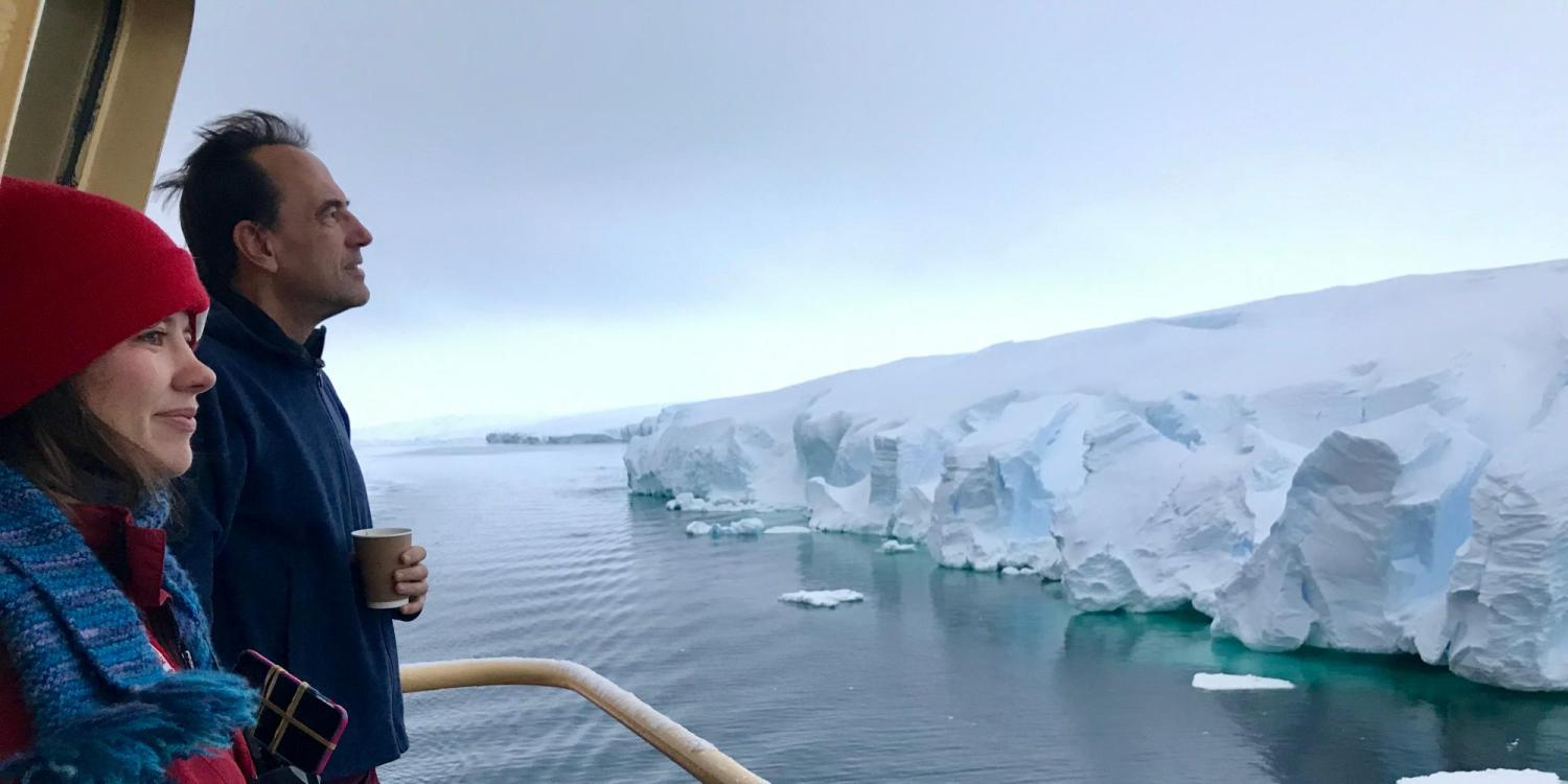Man and woman looking at Antarctic ice from deck of boat