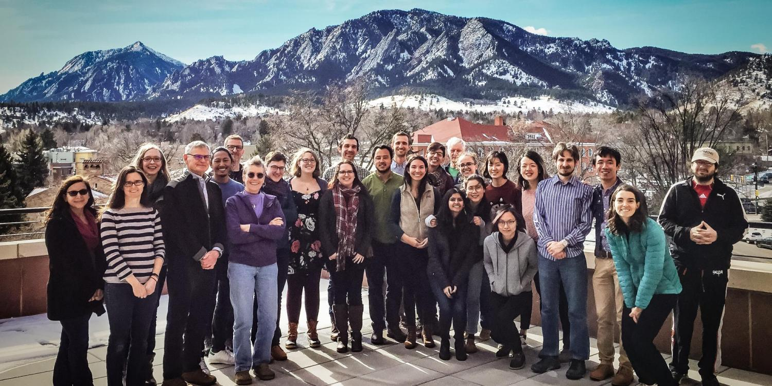 large group of people posing in front of mountain backdrop