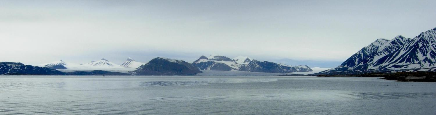 Body of water in foreground; arctic mountains in background