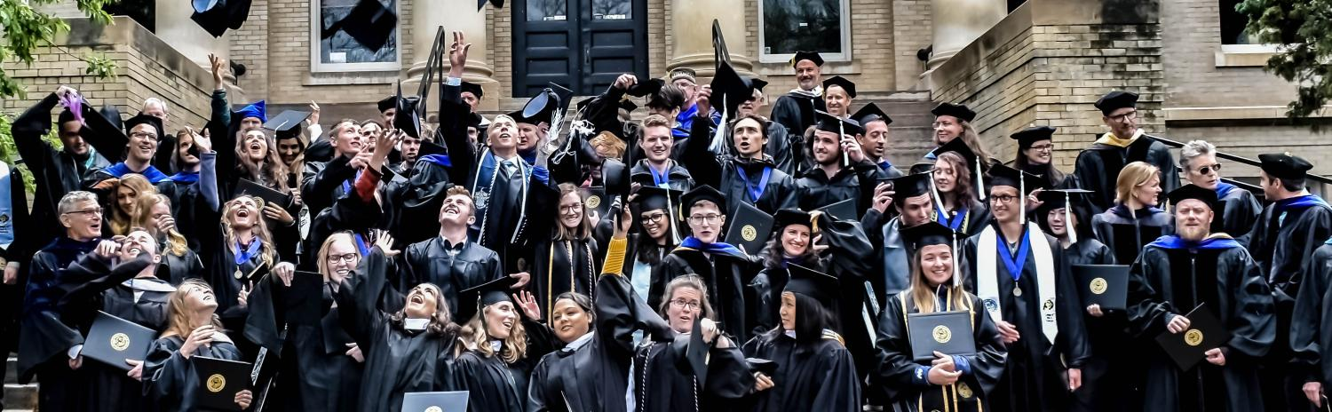 Commencement group photo of student tossing their mortarboards
