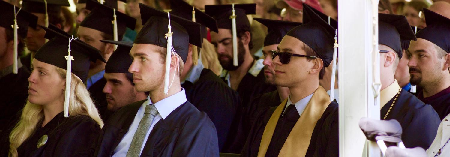 Graduating students, in caps and gowns, seated and listening.