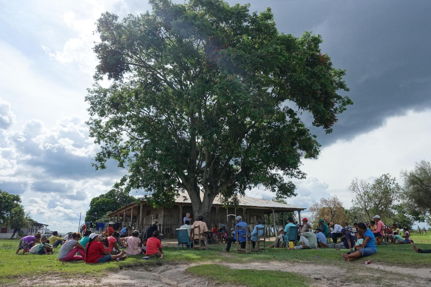 Group of indigenous people in Paraguay sitting under a tree in front of a building