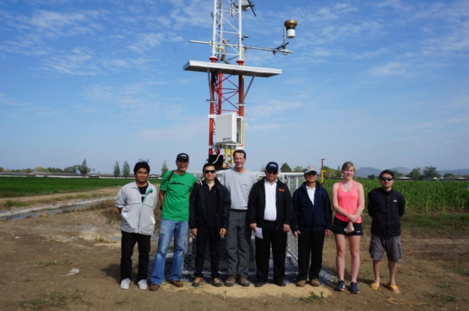 Group of 8 people standing in front of meteorological tower