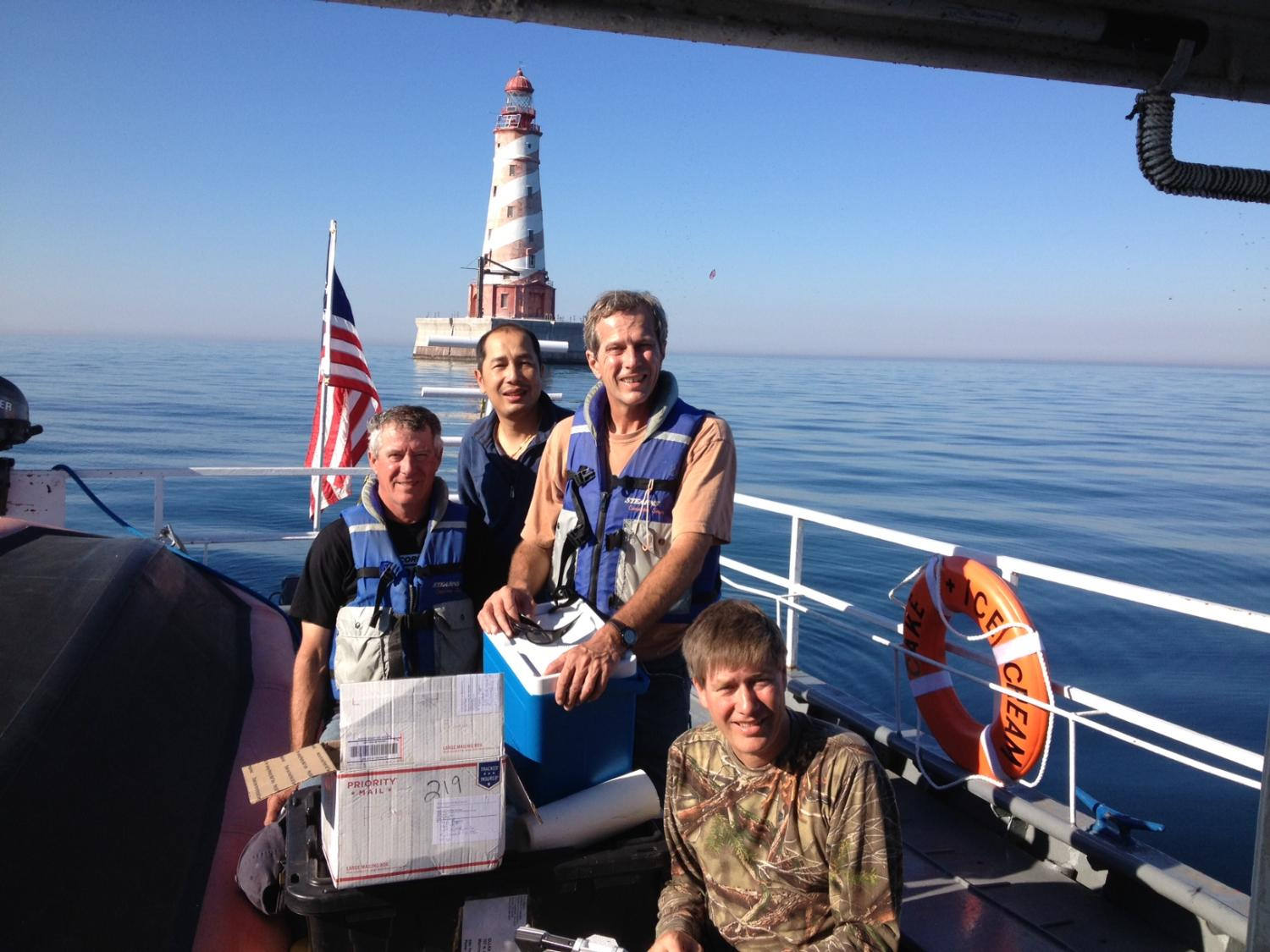 4 men on deck of boat in front of a lighthouse posing for photo