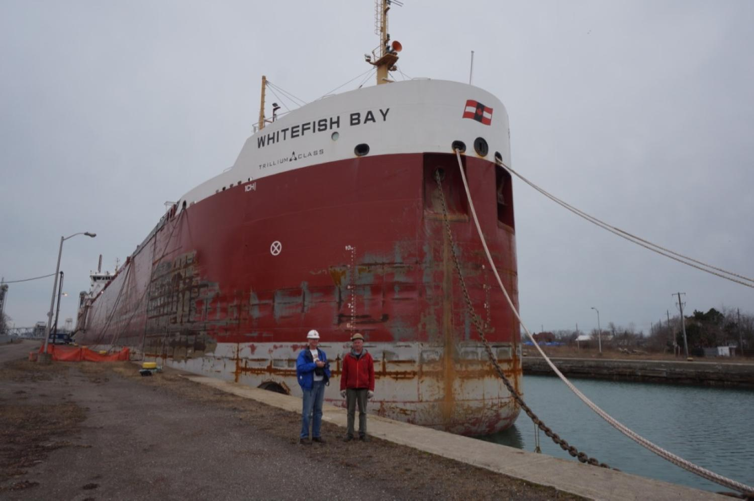 2 men on dock posing in front of large ship