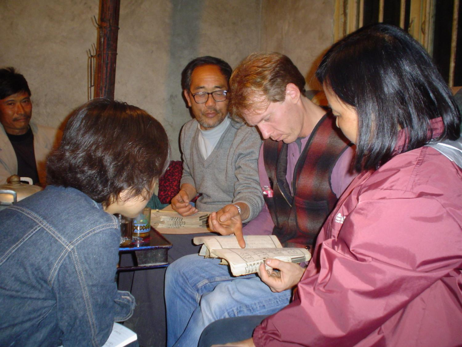 Seated caucasian man examining book with Asian men, woman, and children seated around him