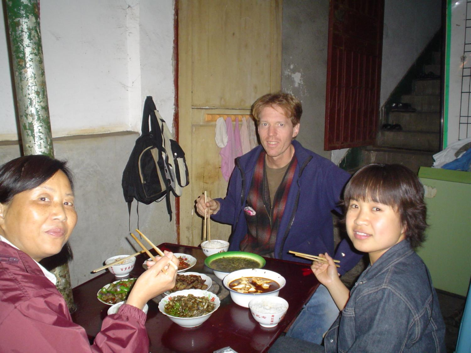 Caucasian man with chopsticks eating dinner with 2 Chinese women