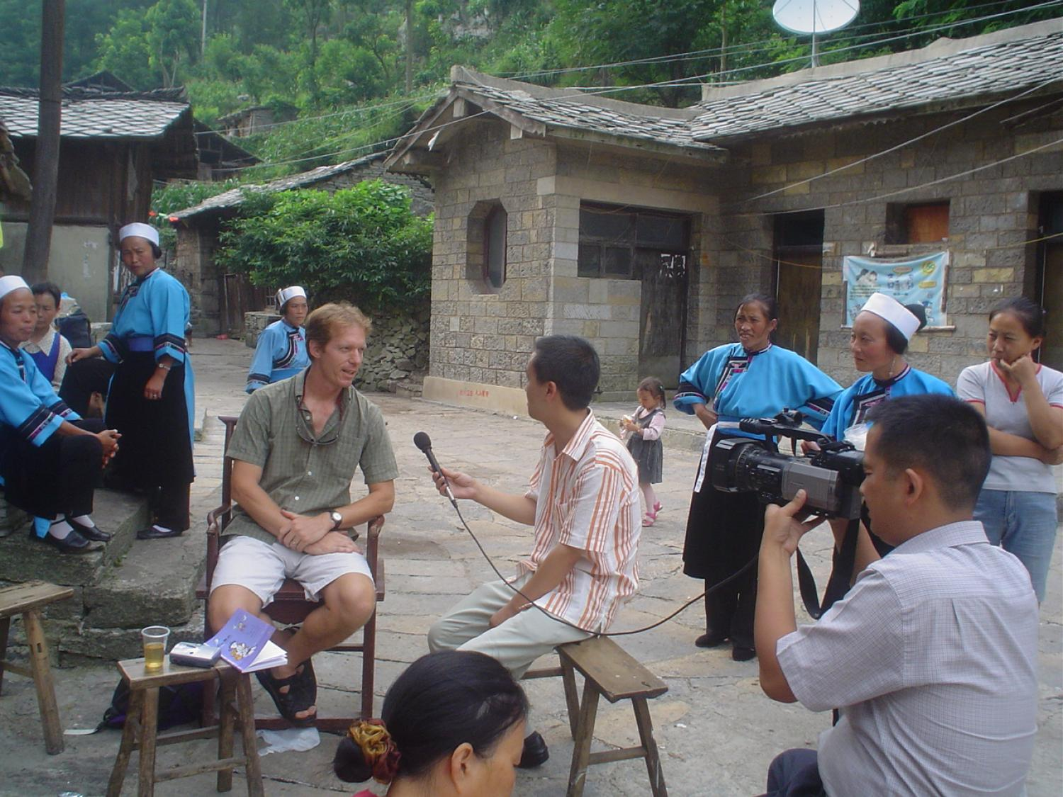 Seated caucasian man in Chinese village next to TV interviewer and camera crew with villagers observing