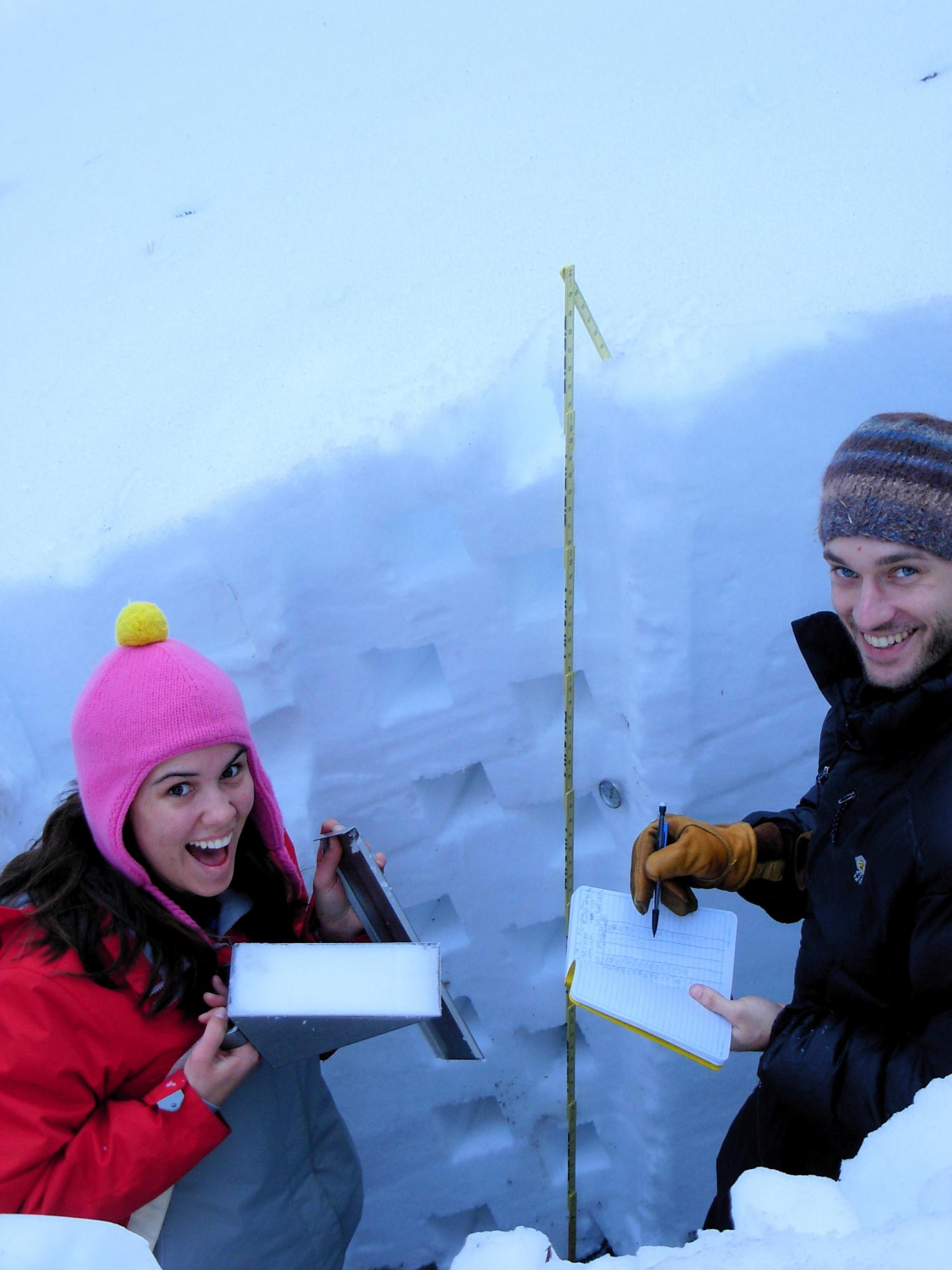 2 students checking snow depth in the mountains