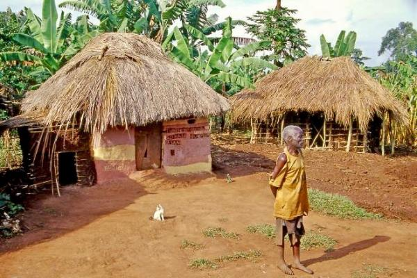 Old man in front of thatched roof hut