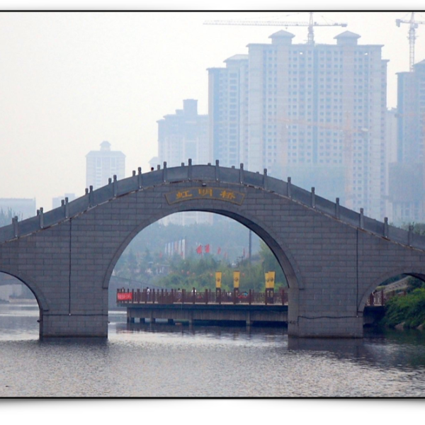 Chinese river with arched bridge, near a big city