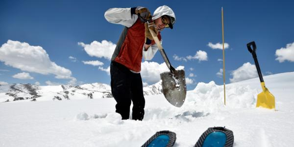 Researcher shoveling in the mountain snow