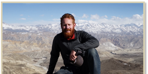 Galen in Mustang, sitting above the upper valley and agricultural region of Nyechung, Mustang District. The northern reaches of the Annapurna-Dhaulagiri Himalaya mountains can be seen behind him.
