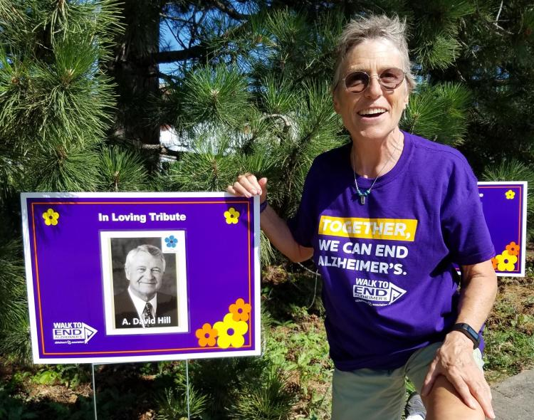 """Woman kneels next to poster with a photo of A. David Hill and the words """"In Loving Tribute"""""""